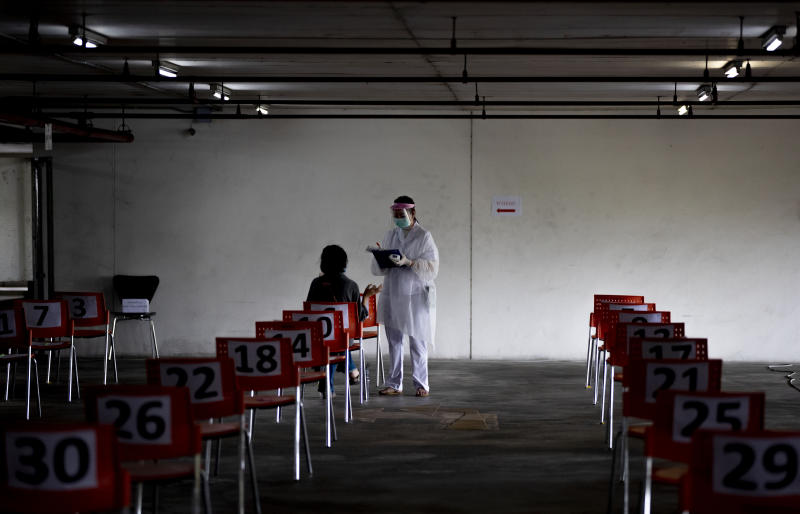 A nurse in protective clothing takes notes from a woman with symptoms of new coronavirus at a carpark that turned into a COVID-19 infection screening center at Chulalongkorn University health service center in Bangkok, Thailand, Wednesday, April 1, 2020. The new coronavirus causes mild or moderate symptoms for most people, but for some, especially older adults and people with existing health problems, it can cause more severe illness or death. (AP Photo/Gemunu Amarasinghe)