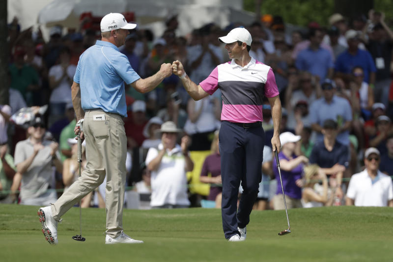 Rory McIlroy, of Northern Ireland, right, is congratulated by playing partner Nate Lashley after McIlroy sank his birdie putt on the 18th green to give him the lead during the third round of the World Golf Championships-FedEx St. Jude Invitational Saturday, July 27, 2019, in Memphis, Tenn. McIlroy finished the day at 12-under par, one stroke ahead of Brooks Kopeka. (AP Photo/Mark Humphrey)