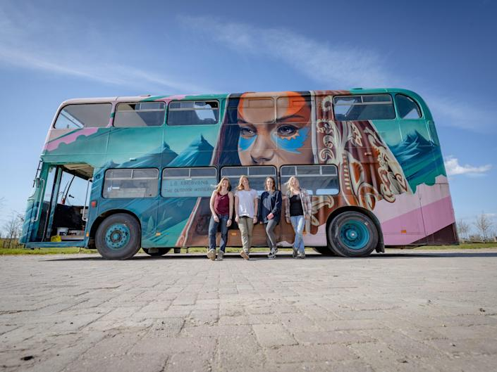the four women in front of the finished double decker bus