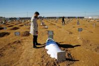 Thikran Kamiran Yousif, 22, visits his father's grave in Kojo