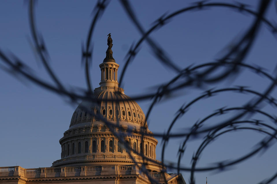 The Capitol is seen through razor wire at sunrise in Washington, Friday, March 5, 2021. (AP Photo/Carolyn Kaster)