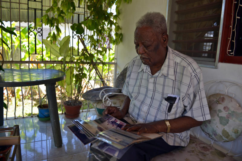"""In this March 11, 2013 photo, pensioner Stephen Batchelor, 89, is shown sitting on the patio of his Spanish Town home looking through a picture album from his days as a community organizer in Birmingham, England, where he lived for decades before returning to his native Jamaica. For years, Jamaica has assisted nationals living abroad to undertake a sort of reverse migration back to the island, but the numbers of Jamaica's so-called """"returning residents"""", who moved to cities like London, New York or Toronto as young adults and dreamt that one day they would return to their sunny island, is steadily dwindling. (AP Photo/David McFadden)"""
