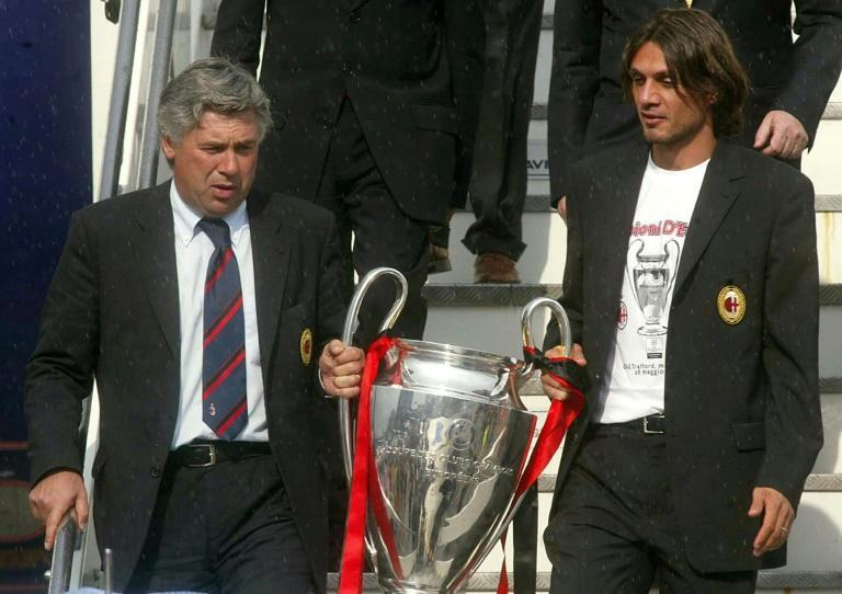 Shared glory: Carlo Ancelotti and his captain Paolo Maldini bring the Champions League trophy back to Milan in 2003