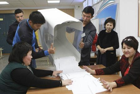 Members of a local electoral commission empty a ballot box at a polling station after a presidential election in Bishkek