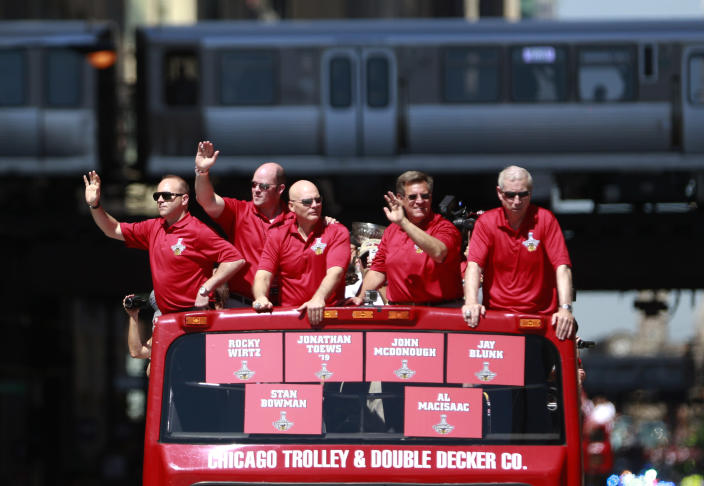 The Chicago Blackhawks' executive staff, from left, General Manager Stan Bowman, Vice presidents Al Macisaac, Jay Blunk, owner Rocky Wirtz, and President Jim McDonough, ride in the 2013 Stanley Cup Champion victory parade down Washington Street Friday, June 28, 2013 in Chicago. The Blackhawks celebrate the team's second championship in four years. (AP Photo/Scott Eisen)