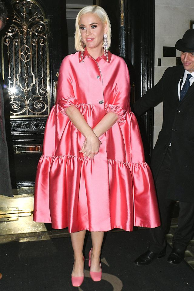 in a pink flounce-hem Lela Rose cape with embellished buttons and pink pumps in London.
