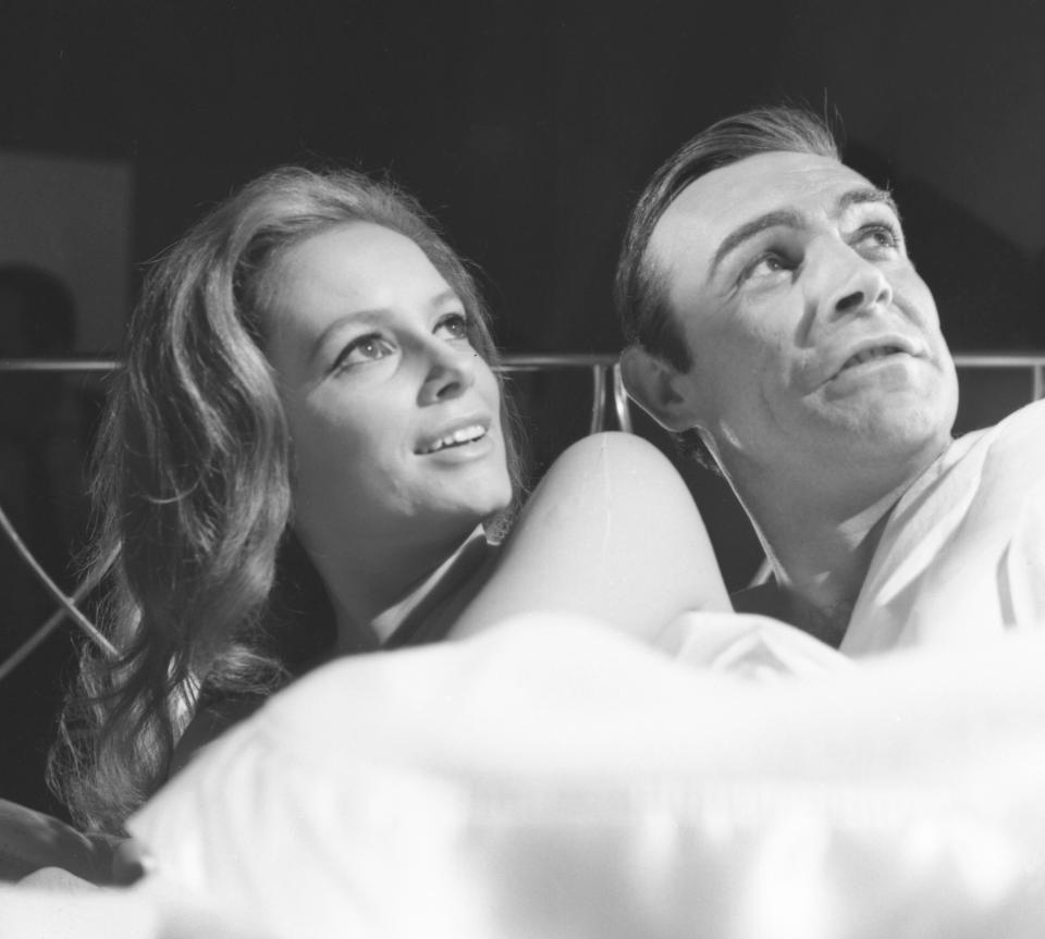 Italian actress Luciana Paluzzi, in the role of Fiona Volpe, in bed for a love scene with secret agent 007 James Bond, played by Sean Connery, during the filming of