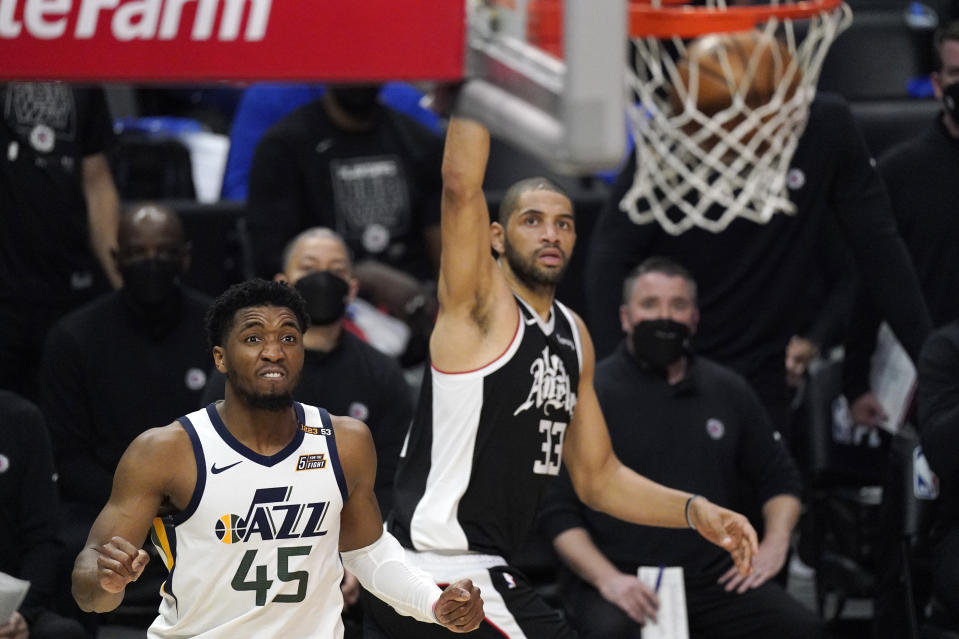 Los Angeles Clippers forward Nicolas Batum, right, scores as Utah Jazz guard Donovan Mitchell watches during the second half in Game 6 of a second-round NBA basketball playoff series Friday, June 18, 2021, in Los Angeles. (AP Photo/Mark J. Terrill)