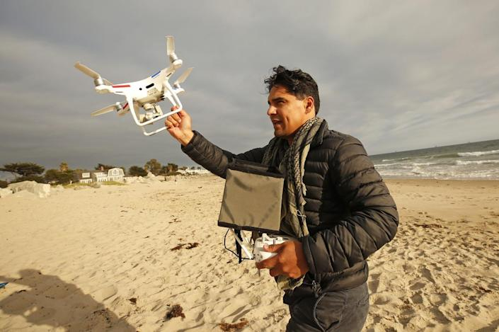 Drone photographer Carlos Gauna grabs his drone to avoid a sand landing