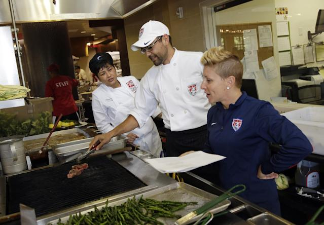 In this photo taken on May 21, 2014, U.S. soccer dietician Danielle LaFata, right, goes over the lunch menu with the team's chef Bryson Billapando, center, and Stanford chef Clarissa Flores during the team's training in Stanford, Calif., in preparation for the World Cup soccer tournament in Brazil. Billpanado cherishes his World Cup experience after surviving the 2012 Colorado theater shooting. (AP Photo/Marcio Jose Sanchez)