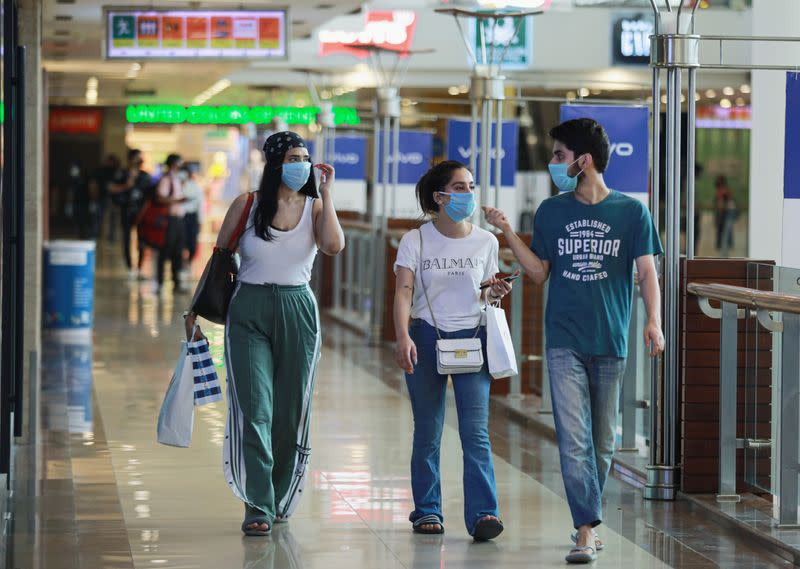 People wearing masks walk with shopping bags inside a mall as India eases lockdown restrictions that were imposed to slow the spread of the coronavirus disease (COVID-19), in New Delhi