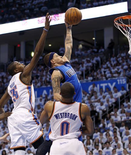 Dallas Mavericks guard Delonte West, right, shoots between Oklahoma City Thunder forward Kevin Durant (35) and guard Russell Westbrook (0) in the third quarter of Game 2 in the first round of the NBA basketball playoffs, in Oklahoma City, Monday, April 30, 2012. Oklahoma City won 102-99. (AP Photo/Sue Ogrocki)