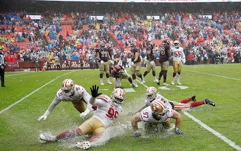 San Francisco 49ers defensive end Arik Armstead (91), 49ers defensive tackle DeForest Buckner (99), 49ers defensive end Nick Bosa (97), and 49ers middle linebacker Kwon Alexander (56) celebrate by sliding on the wet field after the final play against the Washington Redskinsat FedExField - Credit: USA Today