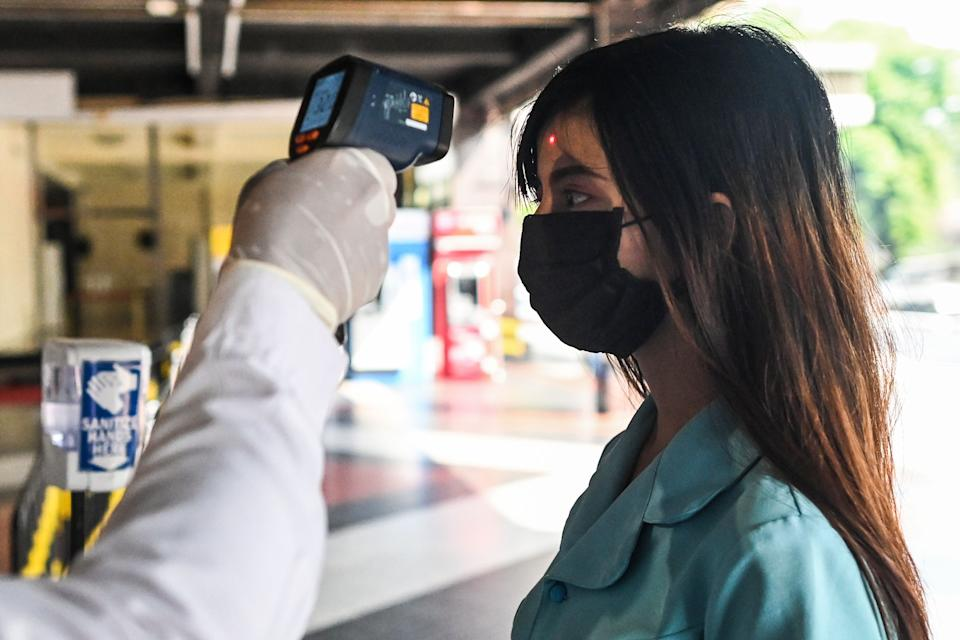 A woman's temperature is taken as a preventive measure against the COVID-19 coronavirus before entering a shopping mall in Yangon  on March 25, 2020. - Myanmar confirmed its first cases of of the deadly novel coronavirus on March 23  after weeks of increasing scepticism over the under-developed southeast Asian nation's claims to be free of the disease. (Photo by Ye Aung THU / AFP) (Photo by YE AUNG THU/AFP via Getty Images)