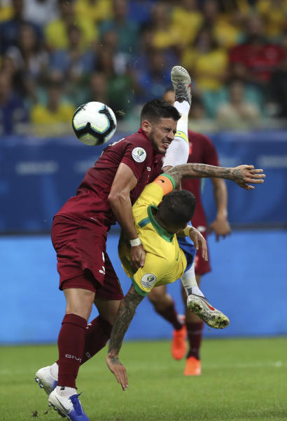 Brazil's Dani Alves, right, fights for the ball with Venezuela's Junior Moreno during a Copa America Group A soccer match at the Arena Fonte Nova in Salvador, Brazil, Tuesday, June 18, 2019. (AP Photo/Ricardo Mazalan)