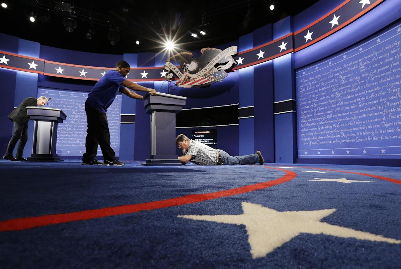 Technicians set up the stage for the presidential debate between Democratic presidential candidate Hillary Clinton and Republican presidential candidate Donald Trump at Hofstra University in Hempstead, N.Y., Sunday, Sept. 25, 2016. (AP Photo/Julio Cortez)
