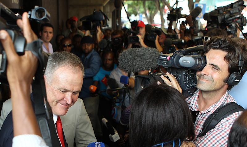 Advocate Barry Roux, left, avoids journalists as he leaves the court after representing Olympic athlete Oscar Pistorius for his bail application at the magistrate court in Pretoria, South Africa, Tuesday, Feb. 19, 2013. Pistorius faces a bail hearing after charged with the shooting death of his girlfriend Reeva Steenkamp, who was cremated in her home town Port Elizabeth on the east coast on Tuesday. (AP Photo/Themba Hadebe)