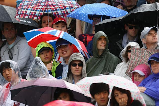 LONDON, ENGLAND - JULY 29: Spectators shleter from the rain during the Women's Team Archery on Day 2 of the London 2012 Olympic Games at Lord's Cricket Ground on July 29, 2012 in London, England. (Photo by Paul Gilham/Getty Images)