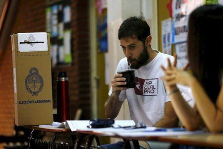 """An election officer drinks a """"mate"""", a traditional herbal infusion, as they wait for citizens to arrive to vote for the presidential election at Buenos Aires, Argentina, November 22, 2015. REUTERS/Ivan Alvarado"""