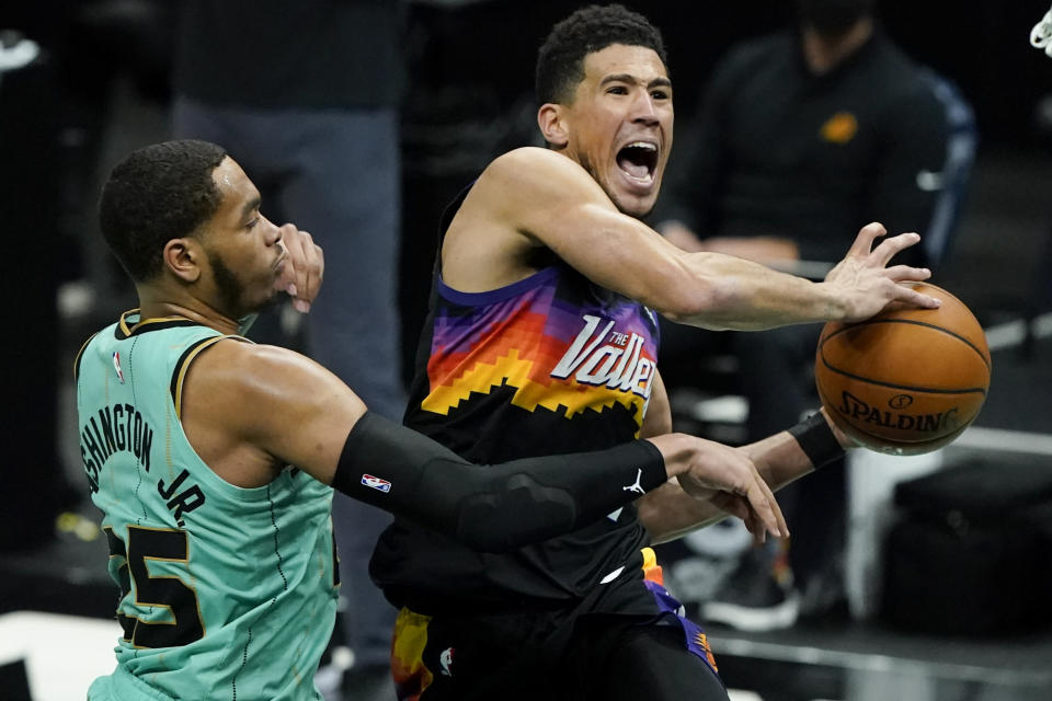 Phoenix Suns guard Devin Booker, right, is fouled by Charlotte Hornets forward P.J. Washington during the second half of an NBA basketball game on Sunday, March 28, 2021, in Charlotte, N.C. (AP Photo/Chris Carlson)