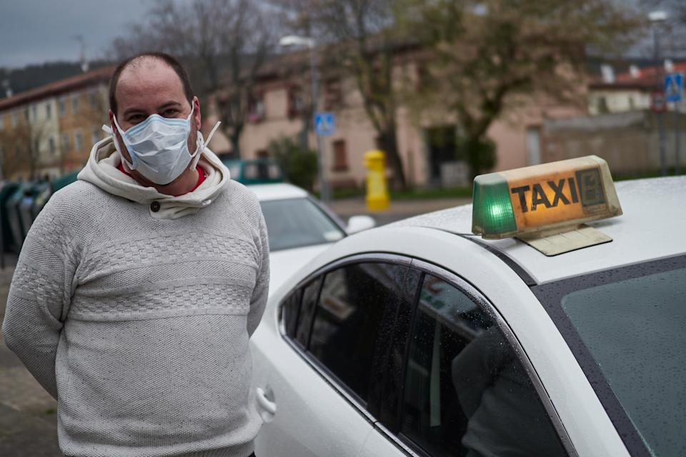 PAMPLONA, SPAIN - APRIL 02: A taxi driver wearing a protective mask poses with his car during the third week of confinement as essential services are allowed despite the confinement due to the coronavirus outbreak on April 02, 2020 in Pamplona, Spain. (Photo by Eduardo Sanz / Europa Press via Getty Images)