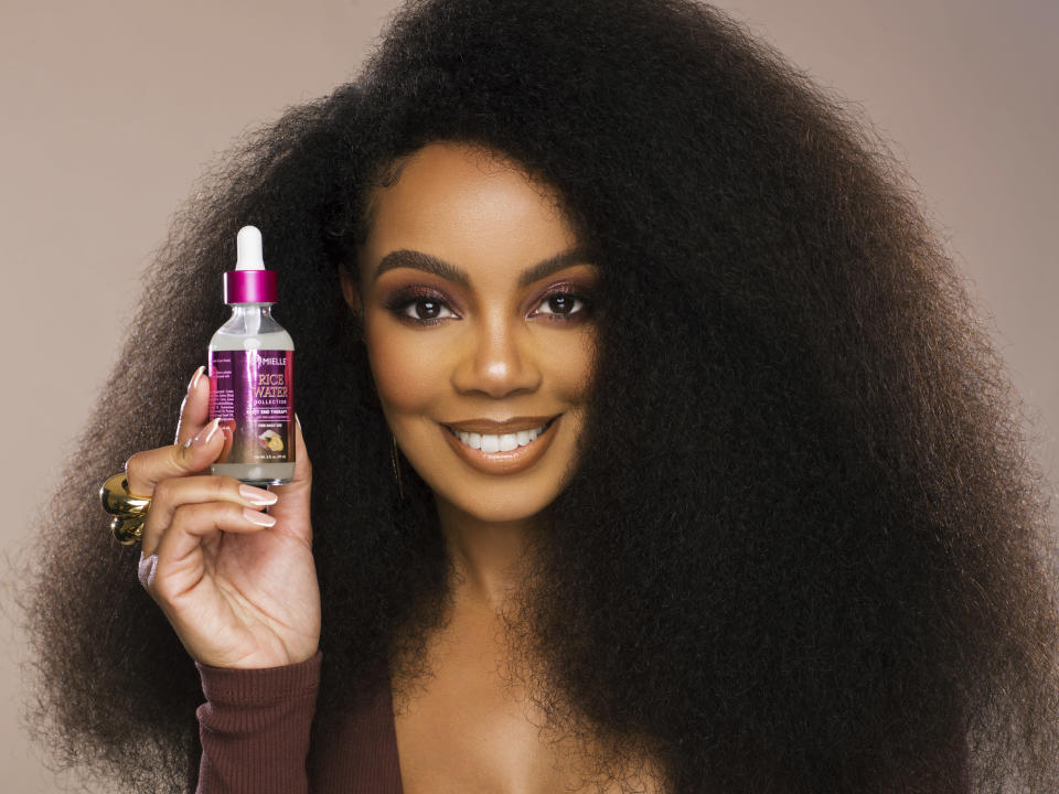 In this photo provided by Derek Blanks Photography Monique Rodriguez poses with one of her company's hair products. Rodriguez co-founded in 2014 Mielle Organics, praised as the fastest-growing Black-owned natural hair care company. Beauty retailers like Ulta and Sephora are ramping up their beauty products from Black-owned companies as a key strategy to combat racial bias in their stores. (Derek Blanks Photography via AP)