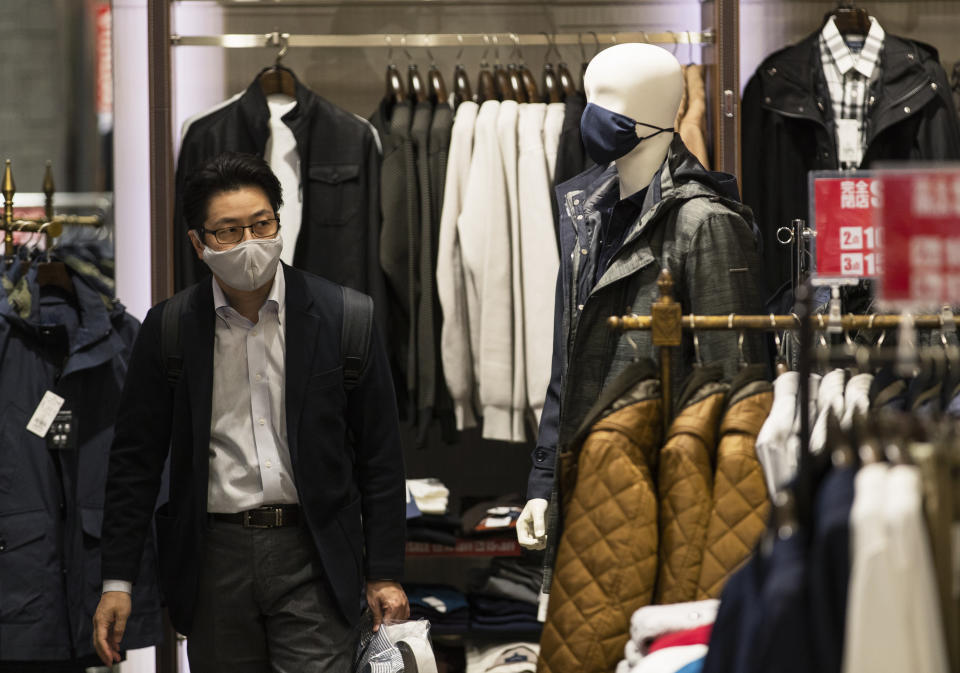 A man wearing a face mask shops around at a clothing store in Tokyo on Thursday, Oct. 29, 2020. (AP Photo/Hiro Komae)