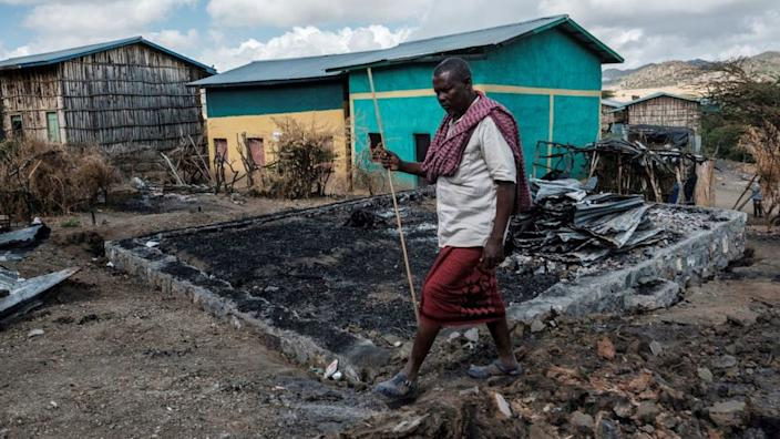 Addis Ciss, 49, walks in front of his destroyed house in the village of Bisopar on December 9, 2020, in the Tigre region of Ethiopia