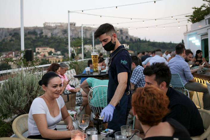 A waiter serves patrons at a bar in Athens, Greece, Aug. 1. Since the country began lifting lockdown restrictions, the number of coronavirus cases has spiked. (Photo: Costas Baltas / reuters)