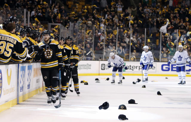 As hats litter the ice and Toronto Maple Leafs players head for the bench, Boston Bruins' David Pastrnak is congratulated at the bench after scoring his third goal of the night, during the third period of Boston's 7-3 win over the Toronto Maple Leafs in Game 2 of an NHL hockey first-round playoff series in Boston Saturday, April 14, 2018. (AP Photo/Winslow Townson)