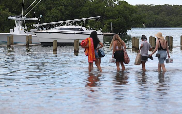People walk to their boat through a flooded parking lot at the Haulover Marine Center before the arrival of Hurricane Dorian on Aug. 30, 2019 in Miami Beach, Fla. The high water was due to King tide which may cause additional problems as Hurricane Dorian arrives in the area as a possible Category 4 storm along the Florida coast.