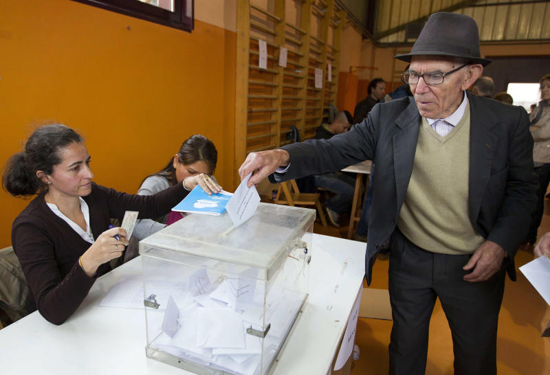 Galician citizen, right, votes in Vigo, northwestern Spain, Sunday Oct. 21, 2012. Almost 4.5 million people will go to the polls Sunday in regional elections in Spain's turbulent Basque region and in Galicia. (AP Photo/Lalo R. Villar)
