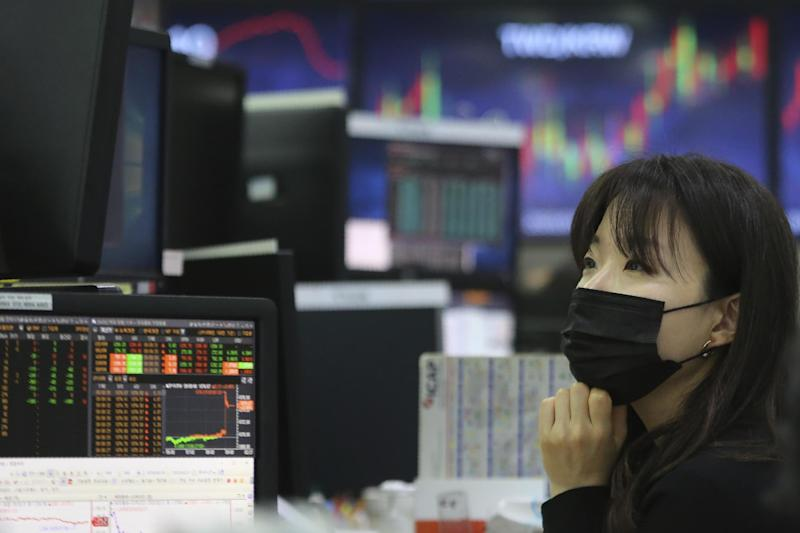 A currency trader wearing a face mask watches monitors at the foreign exchange dealing room in Seoul, South Korea: AP