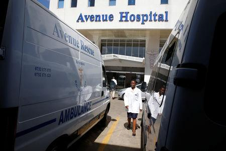 A health worker walks between parked ambulances at the Avenue hospital in Nairobi, Kenya February 1, 2019. Picture taken February 1, 2019. REUTERS/Baz Ratner