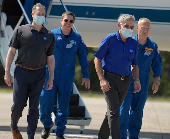 Quarantine measures: Behnken and Hurley were met by officials and reporters wearing masks
