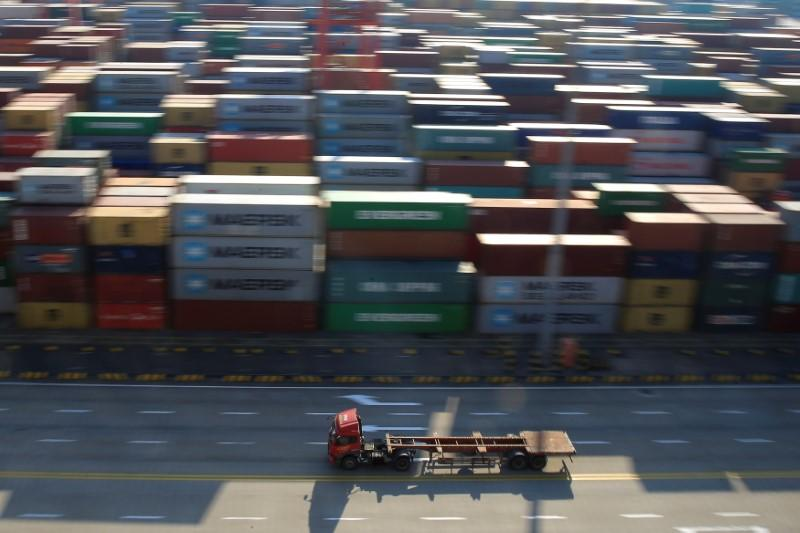 A truck drives past container boxes at the Yangshan Deep Water Port, part of the Shanghai Free Trade Zone, in Shanghai