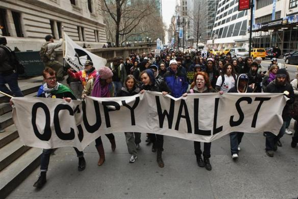 "Members of the Occupy Wall St movement carry a sign during a ""national day of action"" demonstration by the movement in New York February 29, 2012."