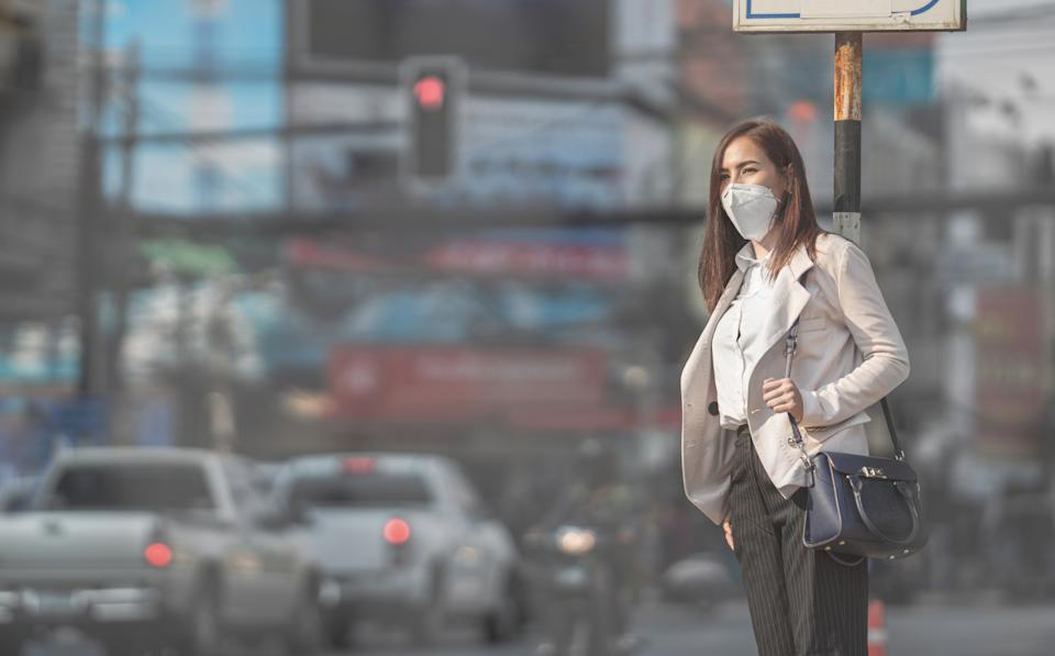 Asian woman are going to work.she wears N95 mask.Prevent PM2.5 dust and smog