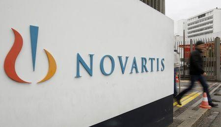 A man walks past the logo of Swiss drugmaker Novartis AG in front of a plant in Basel