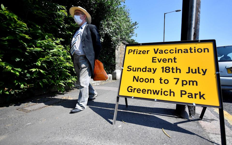 A person walks past a sign informing about a vaccination centre in Greenwich park, London - BERESFORD HODGE /Reuters