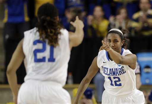 Delaware forward Danielle Parker (12) points to teammate Trumae Lucas (21) after scoring a three-point basket on an assist from Lucas during the second half of a first-round game against West Virginia in the women's NCAA college basketball tournament in Newark, Del., Sunday, March 24, 2013. Delaware won 66-53. (AP Photo/Patrick Semansky)