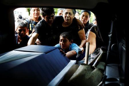 Relatives mourn near the coffin of police officer Juan Jimenez, who was a victim of the earthquake that struck the southern coast of Mexico late on Thursday, during his burial in Juchitan, Mexico, September 10, 2017. REUTERS/Carlos Jasso