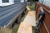 Simon Wolyniec stands near collapsed walls basement of his Manville, N.J., home Sunday, Sept. 5, 2021, in the wake of Hurricane Ida. Wolyniec said that the basement wall collapsed in the early hours of Sept. 2, and shortly thereafter, with the aid of a kayak for his children, he and his family waded into the deep water already inundating the first floor, to safety. (AP Photo/Craig Ruttle)