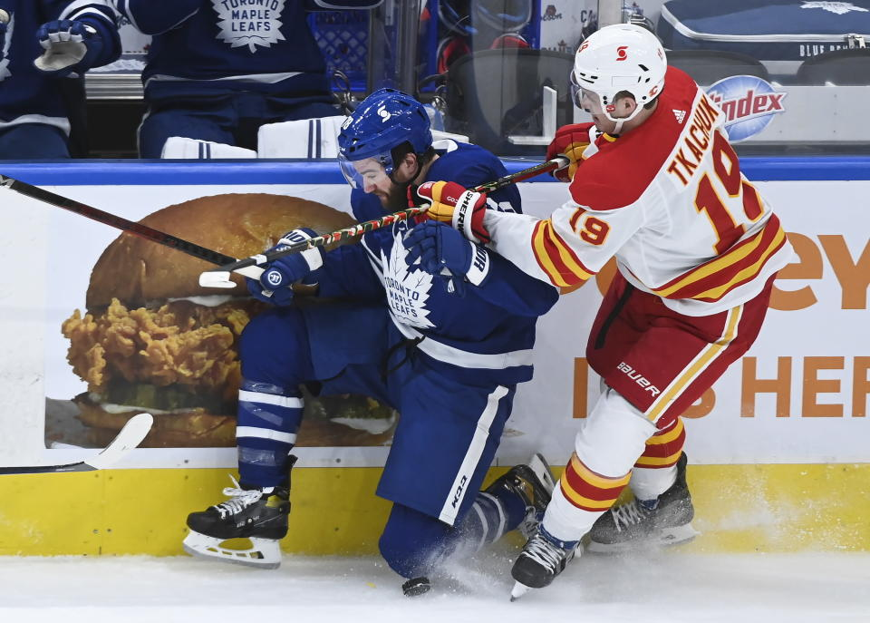 Calgary Flames left wing Matthew Tkachuk (19) takes out Toronto Maple Leafs defenseman TJ Brodie (78) during first-period NHL hockey game action in Toronto, Monday, Feb. 22, 2021. (Nathan Denette/The Canadian Press via AP)