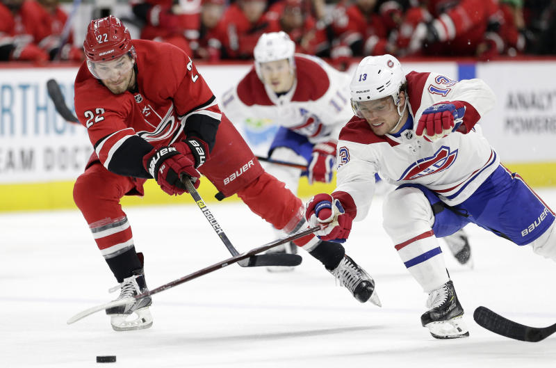 Carolina Hurricanes' Brett Pesce (22) and Montreal Canadiens' Max Domi (13) chase the puck during the second period of an NHL hockey game in Raleigh, N.C., Sunday, March 24, 2019. (AP Photo/Gerry Broome)