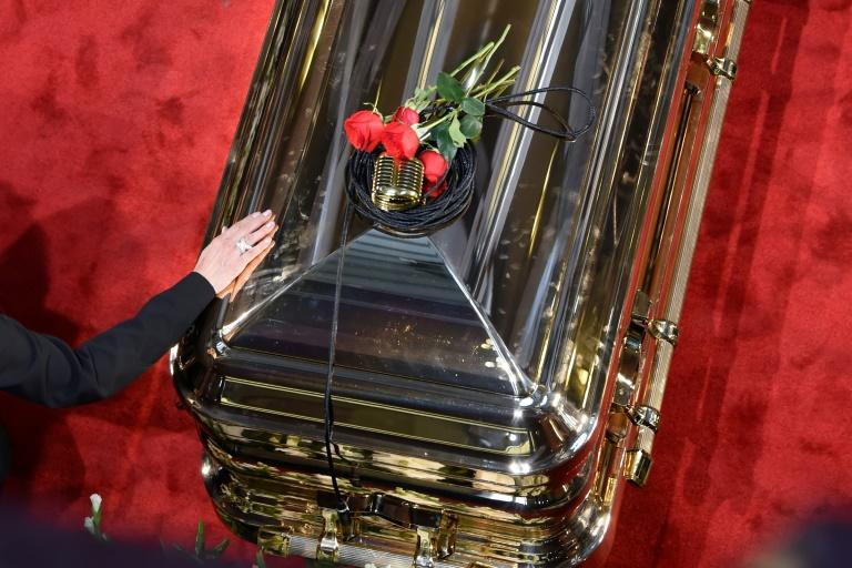 A microphone and roses are seen on top of the coffin of late Mexican singing legend Jose Jose (AFP Photo/Alfredo ESTRELLA)