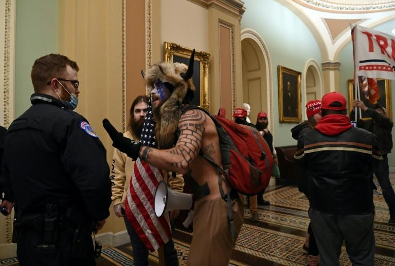 A US Capitol police officer talks to supporters of President Donald Trump who broke into the building on January 6, 2021