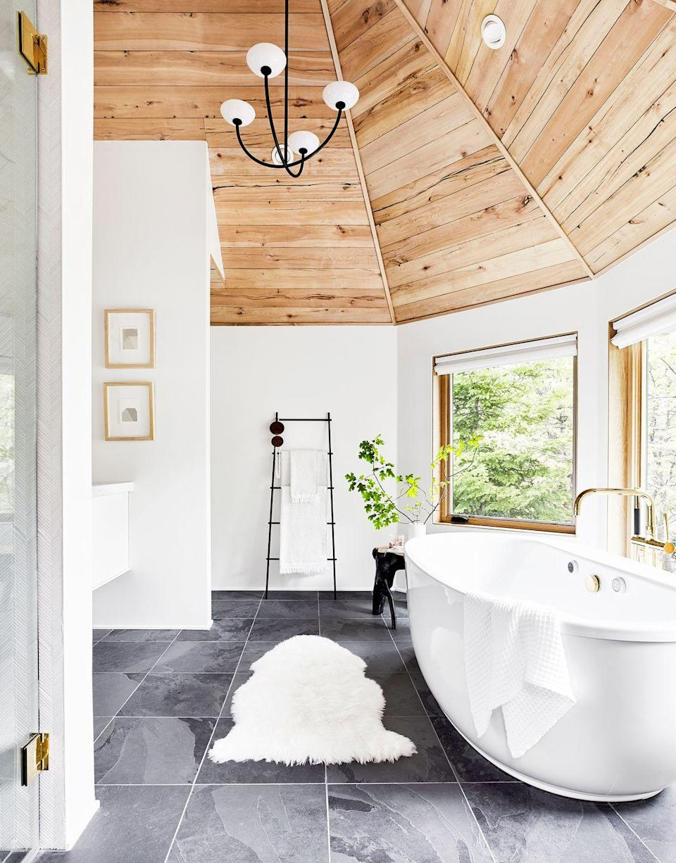 <p>A grand vaulted ceiling is always welcome, but if you want to dial down the drama to make the space feel warmer and more approachable, introduce some wood paneling. The variation in material helps bring the scale down to a more human level, as seen in this bathroom by Emily Henderson Design. </p>