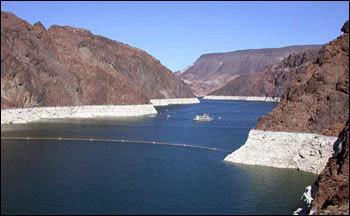 The thick white band ringing Lake Mead's shoreline shows the drop in water levels. The near-vertical walls of Boulder Canyon are just upstream of Hoover Dam.