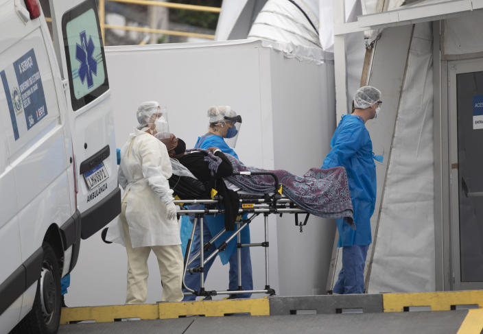 A patient with symptoms related to COVID-19 is brought to a field hospital by workers in full protective gear in Leblon, Rio de Janeiro, Brazil, Thursday, June 4, 2020. (AP Photo/Silvia Izquierdo)